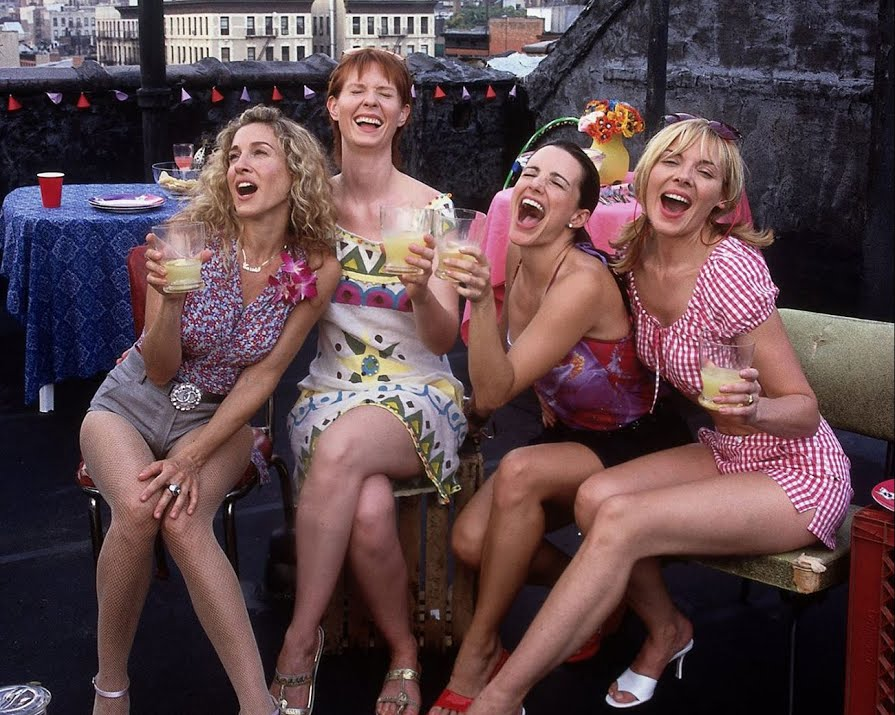 Carrie, Miranda, Charlotte and Samantha on a rooftop laughing